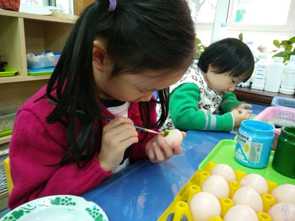 11月2日上午,市委机关幼儿园大班的教室内开办了一次别开生面的绘画活动,用小小的鸡蛋壳绘制自己喜欢的故事。 活动开始了,一位教师为幼儿讲解绘画的要求,另一位教师在一旁忙碌为小朋友准备绘画工具。过了一会儿,原本安静的教室开始暄闹起来,原来桌上放的不是一张张洁白的画纸,而是一只只鸡蛋壳。小朋友个个瞪着眼睛,脸上露出惊讶的神情,大声说着,老师,在鸡蛋壳上怎么画画啊?老师一个鸡蛋壳不够喧闹过后,在老师的讲解下,大家开始动手绘画自己心中喜欢的故事,一个个低着头,小心翼翼的拿着鸡蛋壳,还不时停下手中的画笔,似乎