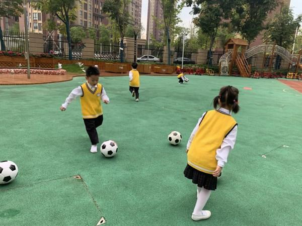 玩是孩子的天性,生活中各种各样的球是诱发幼儿兴趣的天使。2019年10月23日,合肥市市委机关幼儿园教育集团四里河畔园中二班开展了趣味足球户外活动,将足球活动中无穷的乐趣交给孩子,使他们从兴趣中得到满足。 活动初,教师带领幼儿一起交流探讨足球的各种玩法,孩子们络绎不绝的讨论着,有的小朋友说踢足球的时候要用到脚弓的地方,有的小朋友说踢足球的时候要穿足球鞋,有的小朋友说注意安全,还有的小朋友说足球要踢起来,不能用手去拍   接下来,就到了足球时间啦!考虑到中班幼儿的年龄特点,他们还不会相互传球,不能很好的懂